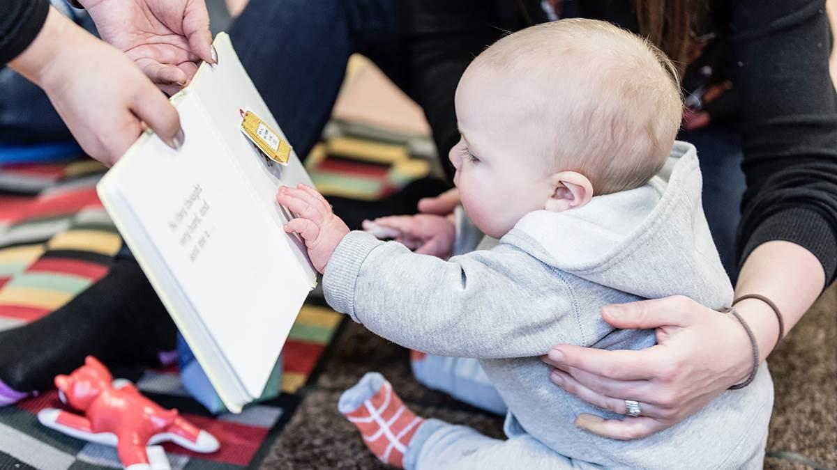 Sitting baby enjoying a book