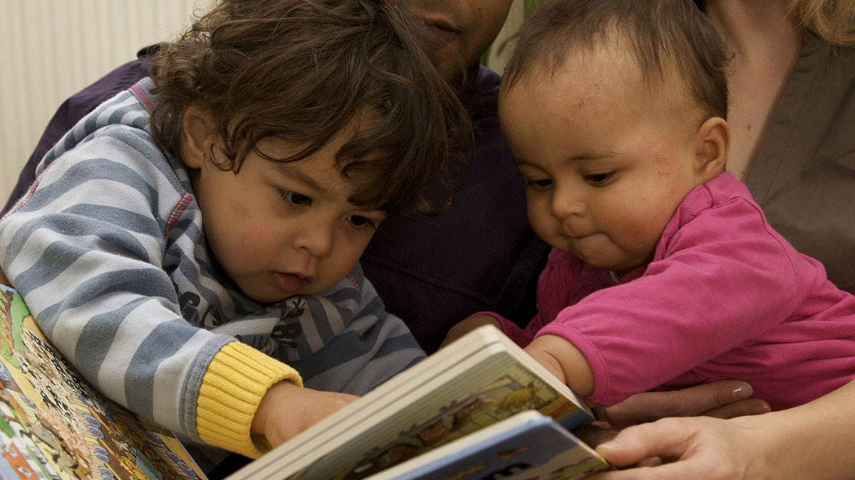 Two babies enjoy reading together