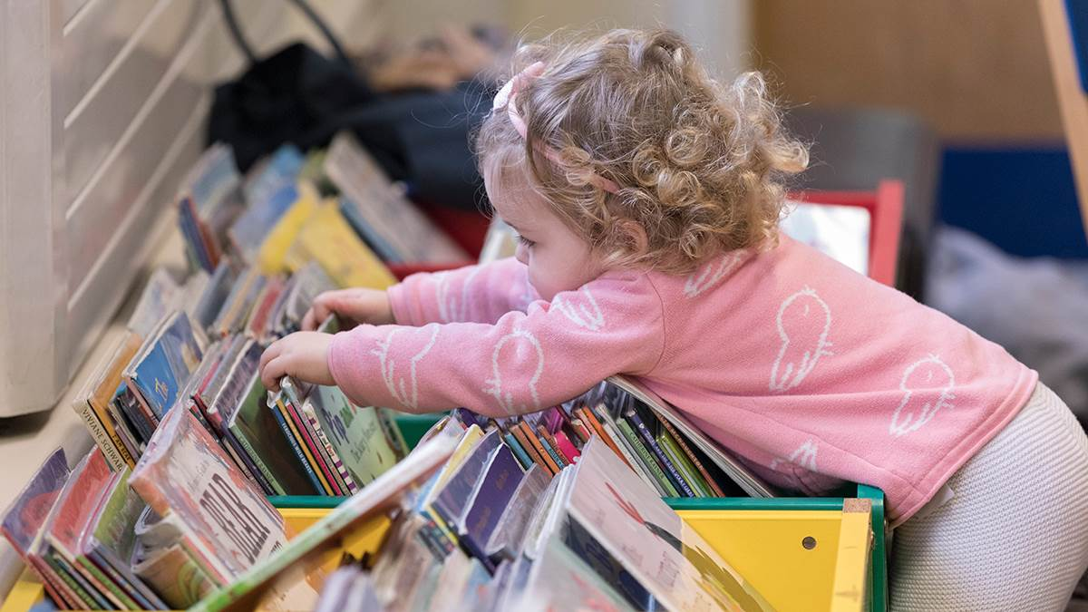 A photo of a girl looking through library books