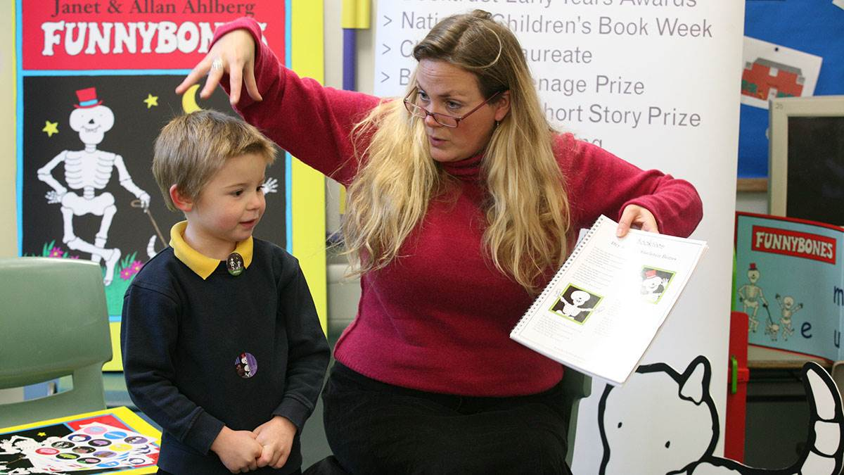 A young student and teacher enjoy reading Funnybones