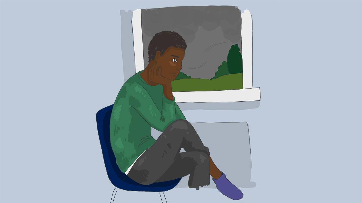 A boy sitting by a window looking sad