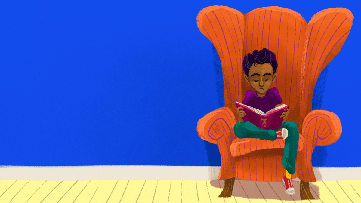 A boy sitting in a chair reading