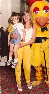 Mothers in yellow pants posing with giant yellow chickens!