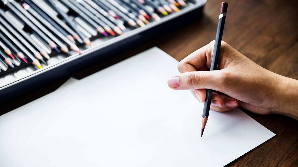 Someone about to draw on a white piece of paper with a set of colouring pencils