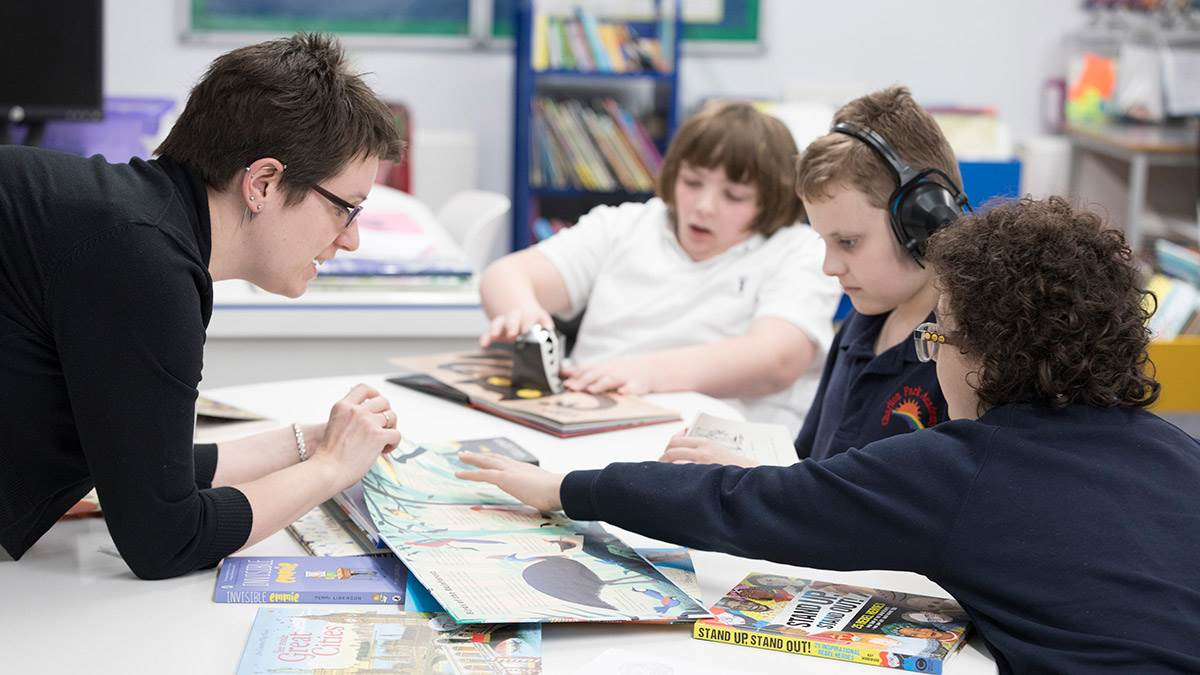 A teacher and students using the Special School Library Pack