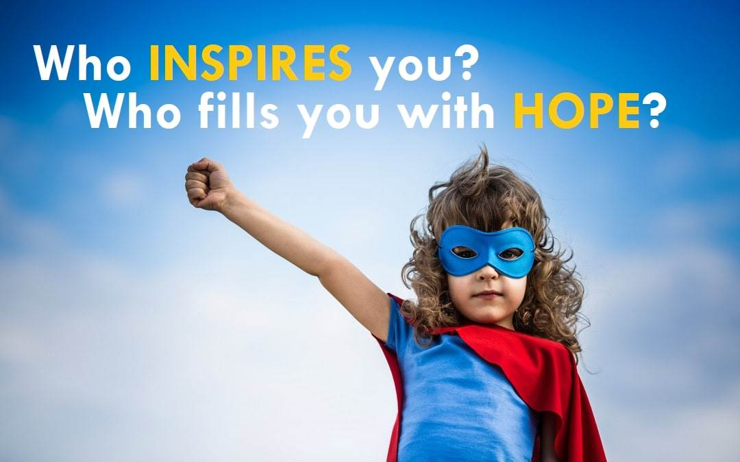"""Photo of a child in a superhero costume with their hand in their air and the caption """"Who inspires you? Who fills you with hope?"""""""
