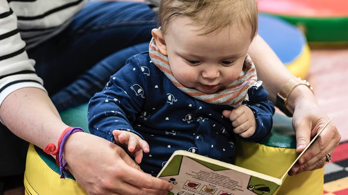Baby and mum sharing a book at a children's centre