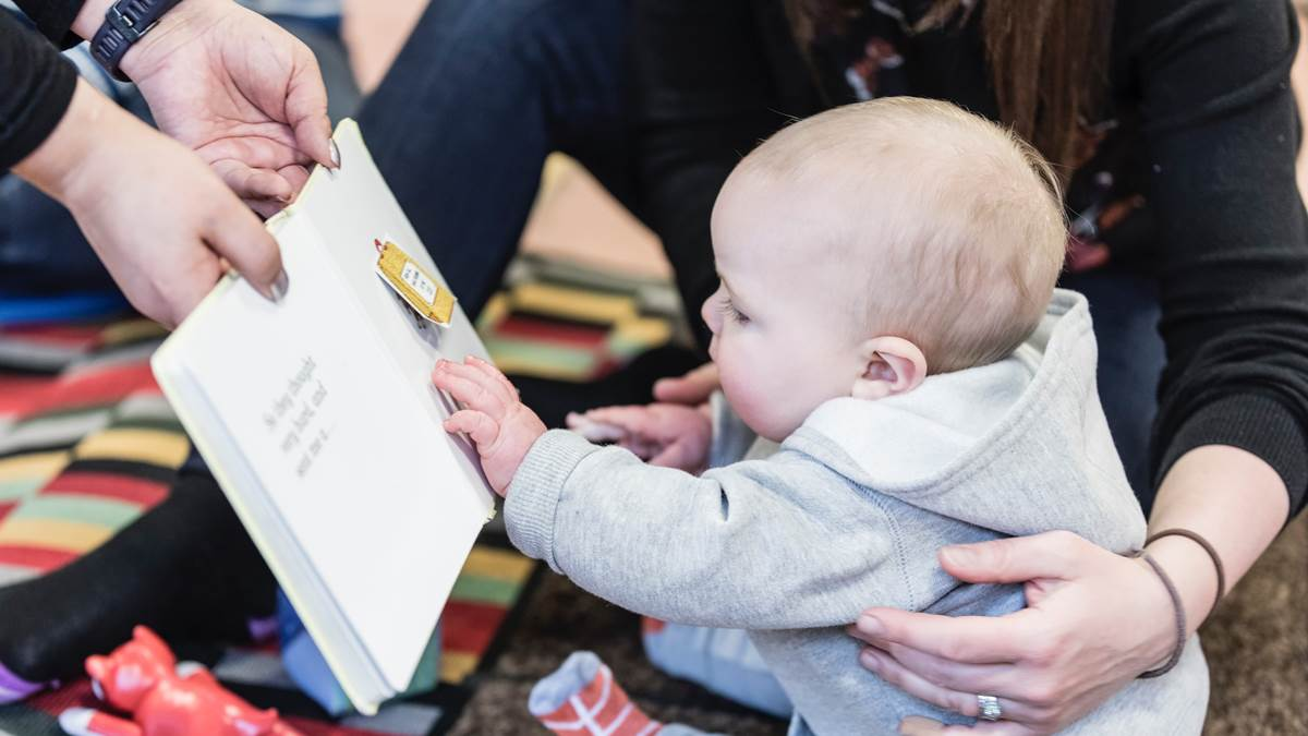 Baby being shown books at a children's centre