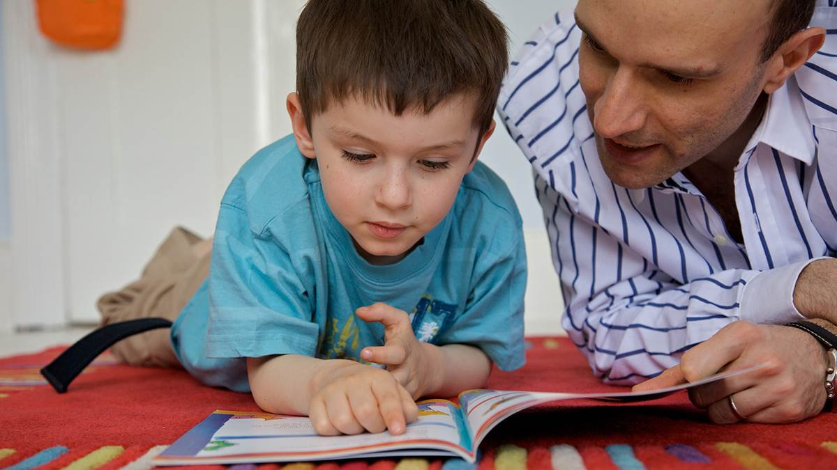 Boy and dad reading lying down