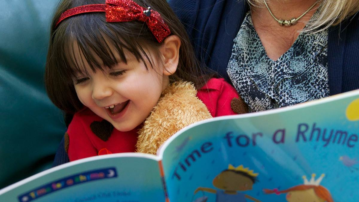 Girl looking at a rhyme book and giggling