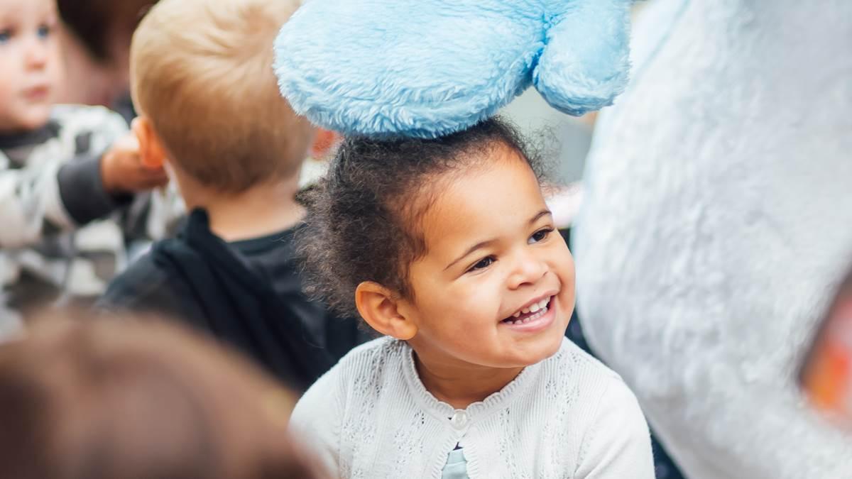 Smiling girl with Bookstart Bear at National Bookstart Week event